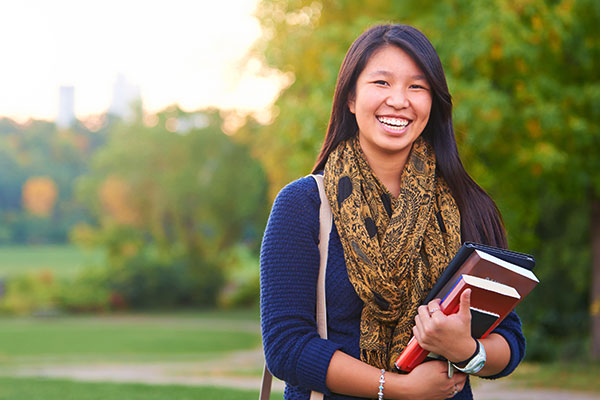female student smiling carrying books